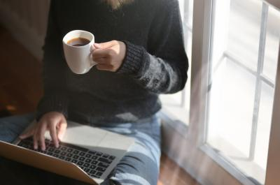 Woman viewing laptop drinking coffee