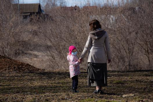 Mother and daughter outdoors wearing protective masks